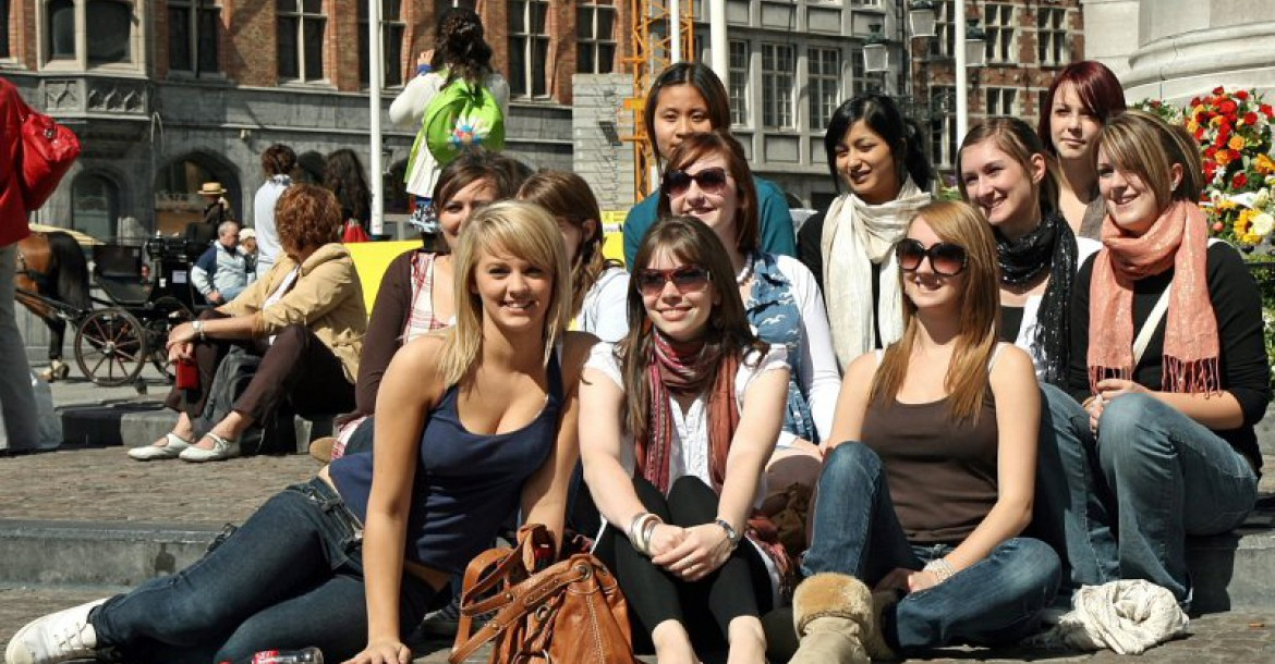 Tourists in bruges enjoy a sunny day